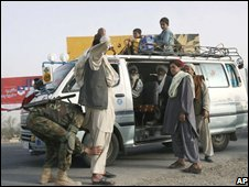 An Afghan soldier, left, searches a man on the way to leaving Arghandab district , 17 June 2008