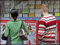 Jovenes miran una cartelera de ofertas laborales