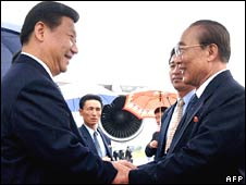 Chinese Vice President Xi Jinping (L) is greeted by senior North Korean official Yang Hyong-sop upon his arrival at Pyongyang Airport on Tuesday