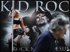 "A commuter walks past as dancers perform on poles atop a promotional open truck to promote Kid Rock""s concert and his new single in London"