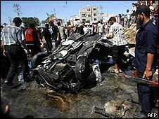 Palestinians inspect the wreckage of a car hit by an Israeli air strike n Khan Yunis, southern Gaza strip