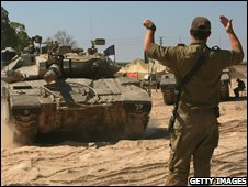 Israeli army officer directs a Merkeva tank onto a transporter, at a forward post close to the border with the Gaza Strip on June 18, 2008 near Kibbutz Ein Hashloshah in southern Israel