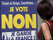Woman walks past a poster during the campaign over the European Constitution