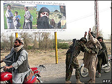 Afghan National Army  searches passengers at a checkpoint near Kandahar on June 17, 2008