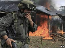 Anti-narcotics police officer in Colombia officer stands by burning coca lab destroyed in anti-drugs operation.