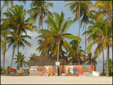 Local huts selling various artworks and paintings on a beach in Zanzibar