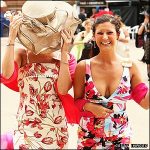 Two female racegoers in colourful dresses