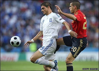 Greek forward Angelos Charisteas is challenged by Spain's Juanito Gutierrez
