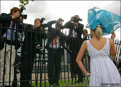 Photographers take pictures of a lady in a hat