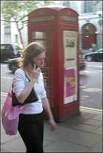 Peatón usando el celular frente a cabina telefónica