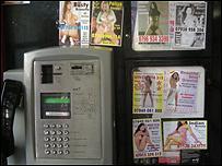 Tarjetas en cabina telefónica.