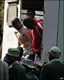 Tendai Biti (in red top) is led into court in Harare on 19 June