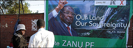 People stand in front of a poster of President Mugabe's campaign on June 9, 2008 in the Zimbabwean capital Harare.