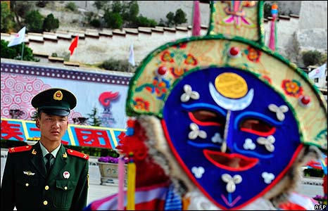 A Chinese paramilitary police officer stands guard in front of a Tibetan performer