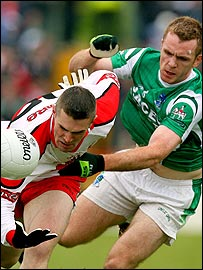 Mark Lynch fights for possession against Fermanagh captain Martin McGrath