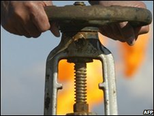 Oil worker turns a valve