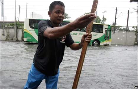 A government worker removes the debris clogging a drainage system of a highway following a flooding brought about by typhoon Fengshen in Manila.