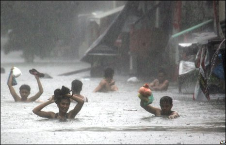 Residents wade through a flooded street in Manila following heavy rains brought about by typhoon Fengshen.