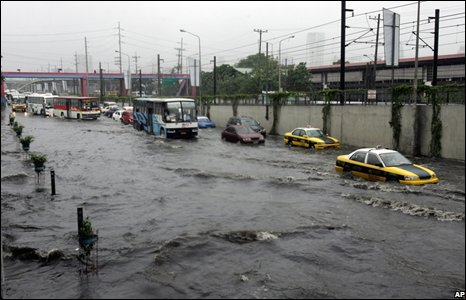 Vehicles negotiate a shallow portion of a flooded highway following heavy rains brought about by typhoon Fengshen in Manila