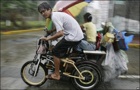 A man and his family brave strong winds in Manila.