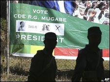 Armed police officers walk past a President Robert Mugabe campaign poster in Shamva, on 29 May.