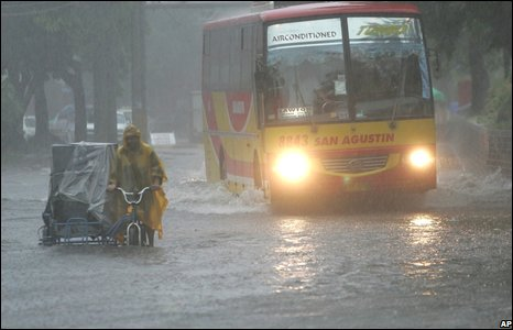 A passenger bus negotiates a flooded road in Manila.