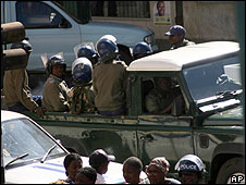 Zimbabwean police ride in the back of a pick up truck during a raid on the opposition Movement for Democratic Change party headquarters in Harare, Monday June 23, 2008.