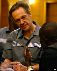 Simon Mann consults with his lawyer during his trial in Equatorial Guinea, 19 June 2008