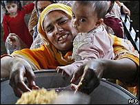 Una mujer y su hijo reciben una ración de arroz en un centro de distribución de alimentos en Pakistán