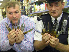 Nadeem Nasir (l) with an officer in his shop