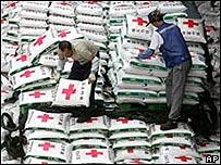 Trabajadores surcoreanos cargan bolsas de fertilizante en un barco de ayuda a Corea del Norte