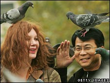 Pigeons sit on the heads of tourists