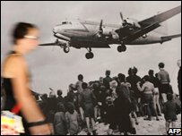 A visitor walks past a picture in a Berlin museum marking the 1948 Berlin airlift