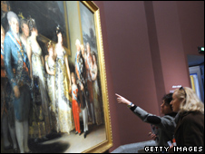 Two museum visitors look at a painting by Goya