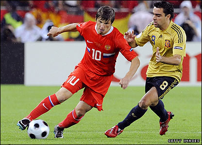 Andrei Arshavin makes life tricky for Spain's midfielder Xavi Hernandez