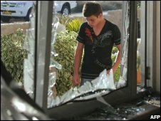 An Israeli youth stands behind a shattered a window following a rocket attack by Palestinian militants from the Gaza Strip in the southern Israeli town of Sderot on June 18, 2008.
