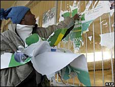 An electoral official removes posters at a polling station