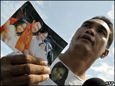 Alexander de la Cruz holds up pictures of missing family members on Sibuyan island on Friday