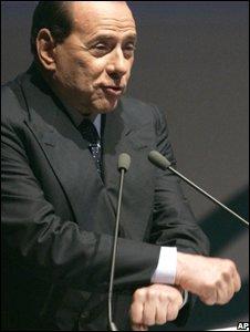 Silvio Berlusconi gestures, mocking having his hands in handcuffs