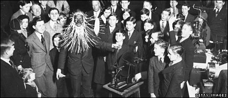 Professor in special electric mask surrounded by school children, 1930