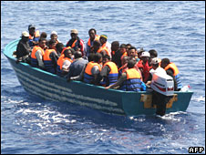 A wooden boat carries some 35 would-be immigrants from Lampedusa on 26 June 2008