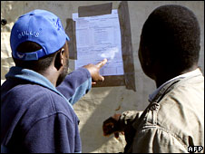 Zimbabweans look at election results posted out a polling station in Harare