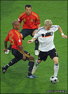 Spain's Marcos Senna and Carlos Marchena shadow German midfielder Bastian Schweinsteiger