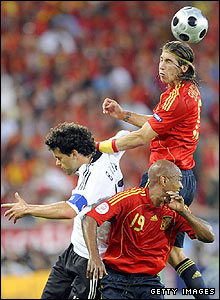 Spanish defender Sergio Ramos heads the ball clear under pressure from Michael Ballack