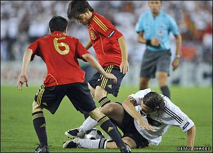 German midfielder Torsten Frings tussles with Spain's Andres Iniesta and David Silva