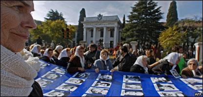 Madres y Abuelas de Plaza de Mayo con la bandera con fotos de desaparecidos