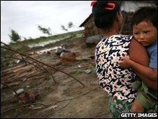 woman holds her boy in  Myasein Kan in the Ayeyarwaddy delta