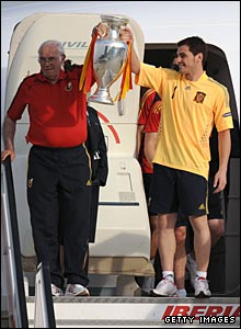 Coach Luis Aragones and captain Iker Casillas carry the trophy down the plane's steps in Madrid