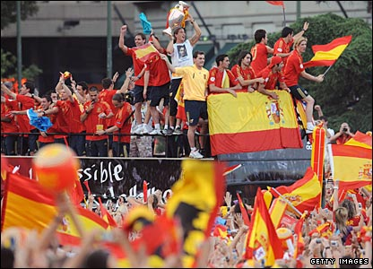Fans celebrate as the Spanish team drive past on an open-top bus