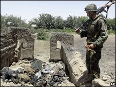 Afghan soldier by the bodies of Taleban militants